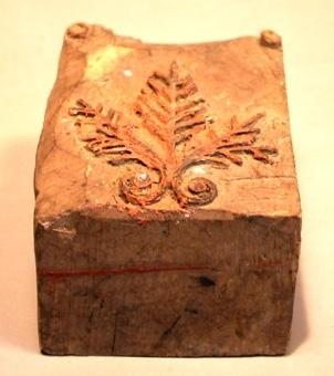 Tryckstock för tapet av trä. Tryckstrocken har utskuret mönster i form av tre bladmönster i en bukett.