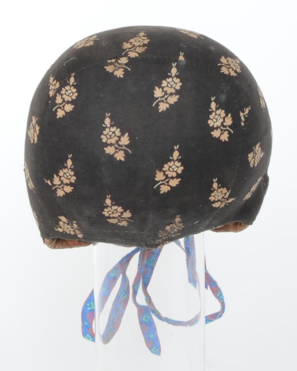 Bindmössa med yttertyg av småmönstrad bomull med brunt som bottenfärg, foder av tuskaftvävt linne. Mössan är kantad med ett rött sidenband och har två maskinvävda bomullsband till knytband.