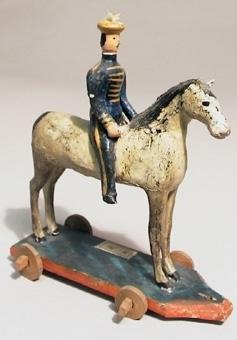 Leksaksryttare av trä, målad. Hästen vit med svart man och svans, ryttarens uniform blå med gula revärer och mössa. Står på platta med hjul. Plym saknas. Hästens färg något flagnad. Betsel saknas