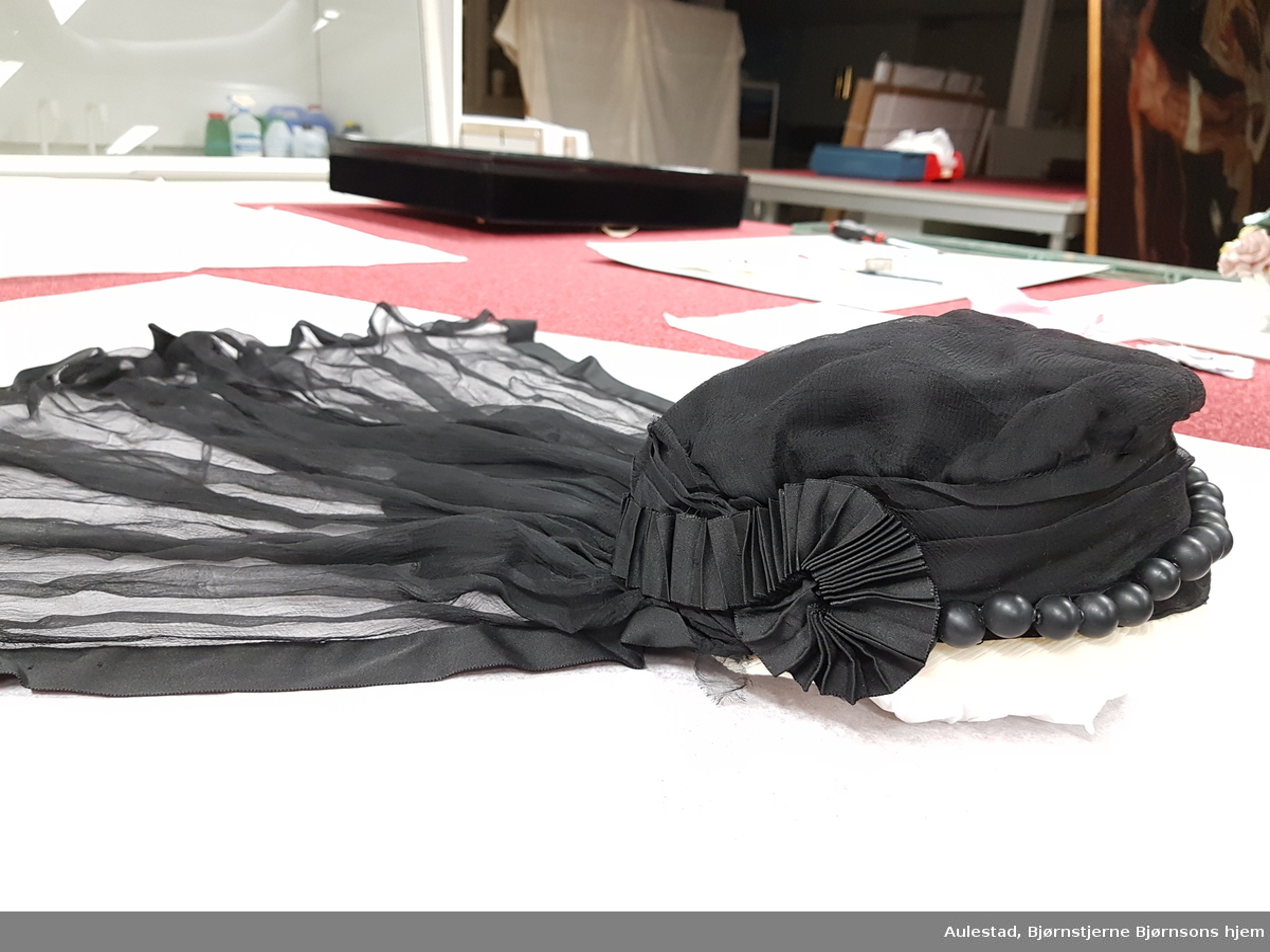 Kappe der pullen har tre lag stoff, ytterst chiffon, krafigere stoff innerst. Pullen er avstivet med metalltråd. Foldelagt chiffon i front med 21 store svarte perler tredd inn på metalltråd. Hvit plissert kant mot issen. Plissert silkebånd bak og som ender i rosetter ved ørene. Bak fra pullen er det festet et trekantformet stykke som danner overgang til sløret. Dette er dekket med chiffon. Selve sløret er også av chiffon kantet med satengvevde silkebånd.
