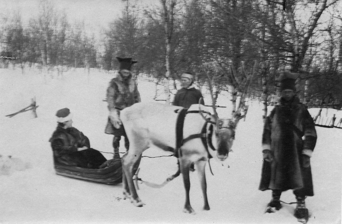 Ellisif Wessel sittende i pulk, tre samer, en kvinne og to menn, står ved siden av. Den ene mannen er sannsynligvis Ole Johnsen Must.