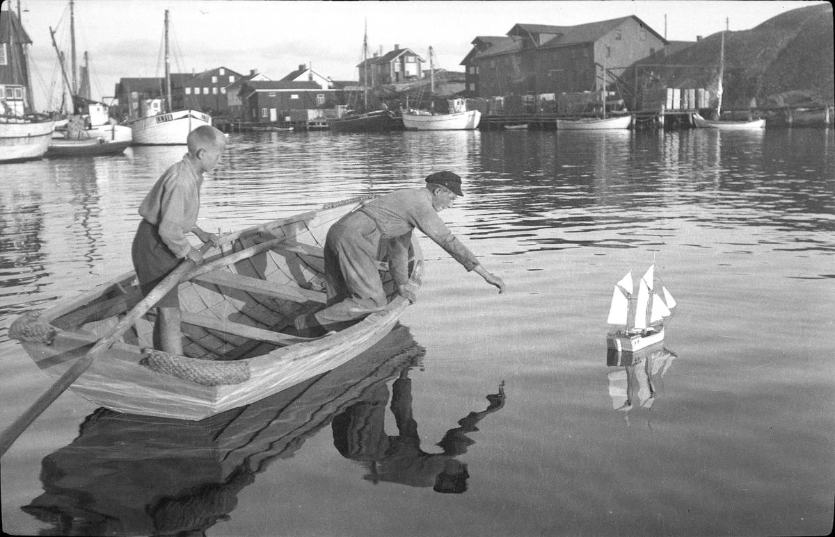 Fiskarpojkar lekande med båtmodell i Smögens hamn.