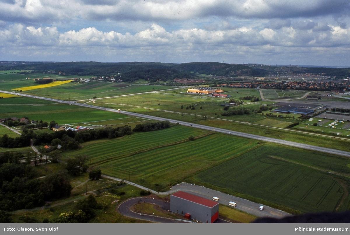 Söderleden går genom jordbrukslandskapet i Fässbergsdalen, Mölndal, i juli 1985. Vy från Riskullaverkets skorsten. I förgrunden ses Riskullaverkets inlastningsbyggnad för kol eller torv, i mitten Kapp-Ahl och till höger Lärarhögskolan och Solängen. FD 1:31.