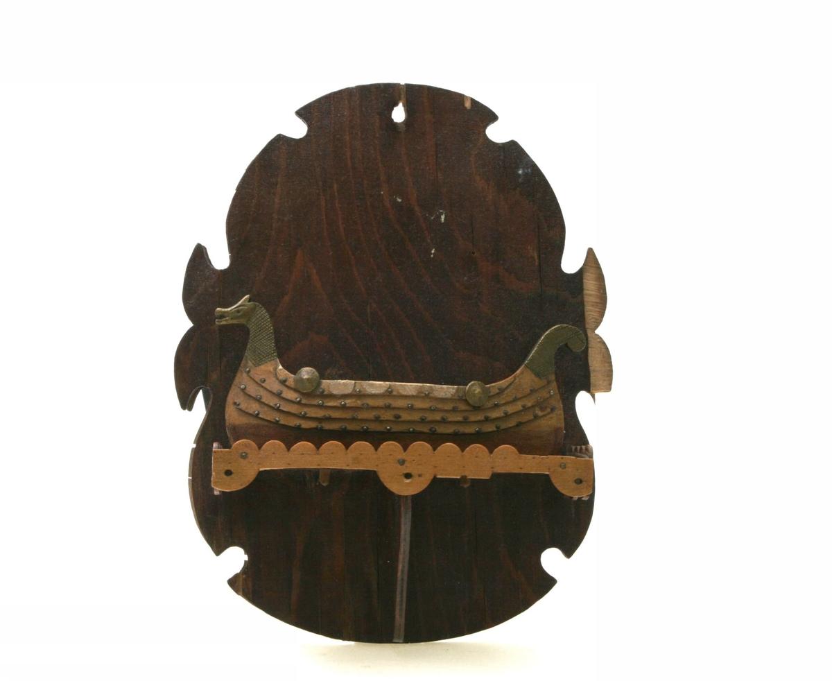 Veggplakett i finer formet som et skjold. På skjoldets nedre del en hylle med utskårne elementer i finer hvor et vikingskip hviler. Skipet er utført av massivt tre, med utskårne skipsbord for å illudere klinkbygging. Kun babord side er utfromet. Små metallstifter illuderer klinsømmen. Skipet har dragehode. Skjoldrekken har to skjold bevart av opprinnelig seks.Skipet har hull for mast og seil. Dette er ikke bevart.