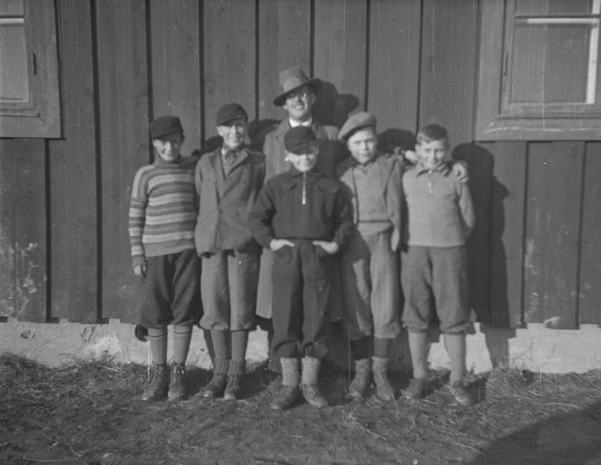 Fem gutter og en mann utenfor et hus.