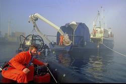 """En mann kjører bort fra dykkerskipet """"Strilborg"""" i en liten"""