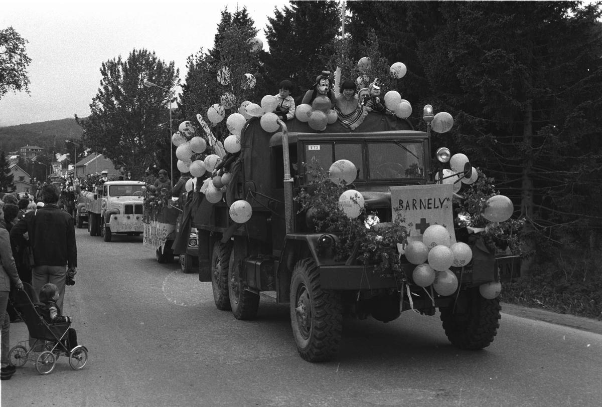 """Opptog med utkledte unger bakpå lastebiler på """"Barnas Dag""""."""
