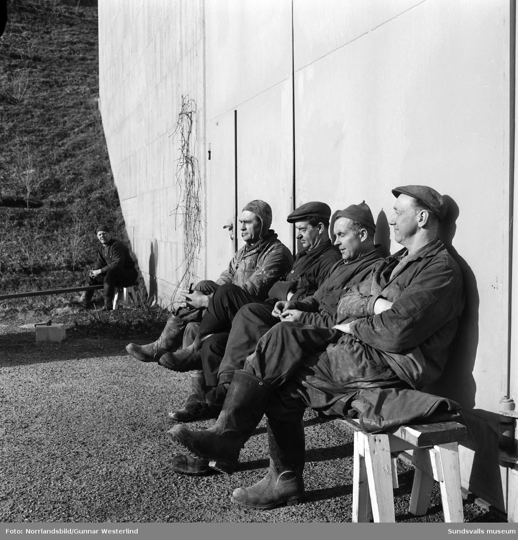 Fem anställda vid Bergeforsens kraftverk tar en paus i vårsolen utanför byggnaden.