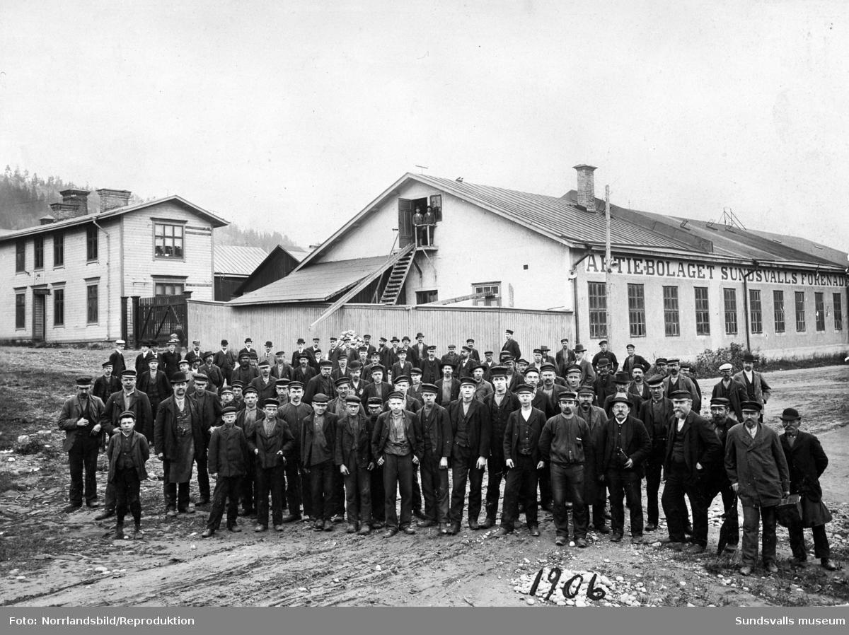 Reproduktion av ett gruppfoto från 1906 med arbetare vid Aktiebolaget Sundsvalls Förenade Verkstäder. Bilden är tagen vid dåvarande byggnadens västra ände.