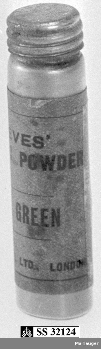 Kapsel av metall med skrukork. Kapselen inneholder metallpulver.
