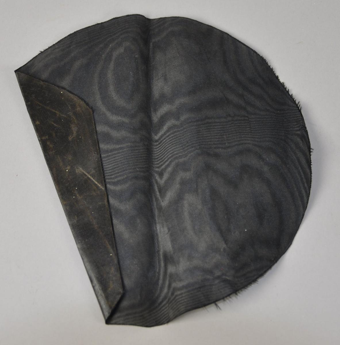 Rundt hattefor av svart silke. Stoffet har merker etter bretting.
