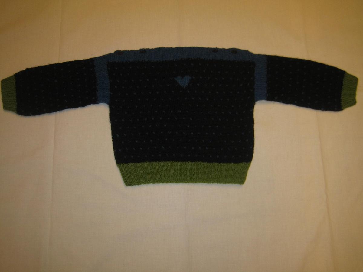 """Tröja slätstickad i svart, grönt och blått med muddar i nederkant, ärmar både början och slut och rakstickad halskant i resårstickning. Nederkant och ärmmuddar är i grönt och halskant och ärm mot isättning i blått. För övrigt är tröjan svart med blå prickar över hela. Tröjan är dekorerad med ett blått hjärta på framstycket. På halskanten är det fyra knapper och knapphål. En lapp är påsydd med texten """"LINGON O BLÅBÄR ST C 80 1 ÅR"""""""