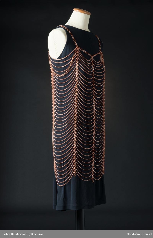 """Smycke i form av kedjor i rödaktig metall. Kedjorna bildar tilsammans formen en klänning eller tunika. Sex vertikala något grövre kedjor sammanlänkade med en mängd tunnare horisontella kedjor. Upptill """"axelband"""" och kant av en grövre kedja.  /Leif Wallin 2018-00-09"""