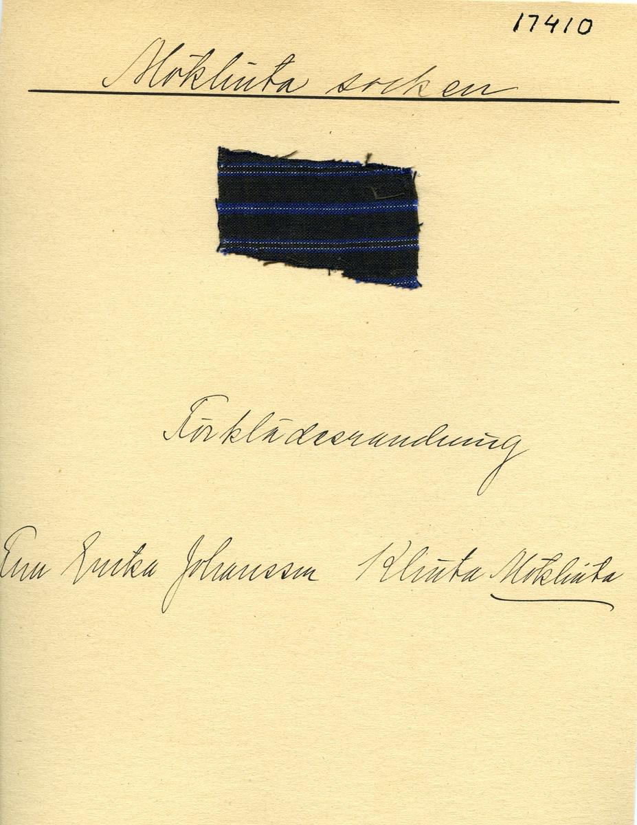 Anmärkningar: Vävprov Olga Anderzons samling. Förklädesrandning. Fru Erika Johansson Klinta Möklinta. Vävprov av bomull i tuskaft, randigt i vitt och blått på mörkblå botten. L. 570 540 Br. 350 450