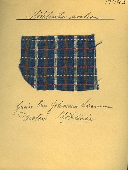 Anmärkningar: Vävnadsprov Olga Anderzons samling. Fru Johanna Larsson, Wreten Möklinta. Vävprov av bomull i tuskaft, rutigt. Varpen är randad i blått, brunt och vitt. Inslaget har smala ränder i rött och vitt på blå botten. L. 1060 970 Br. 780 560