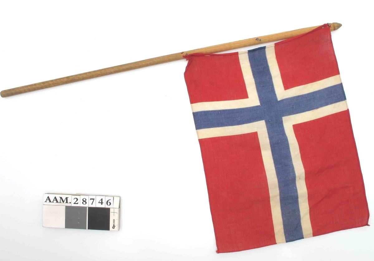 Trestang med påstiftet trykt norsk flagg. Stiftingen er fornyet, men dårlig utført.