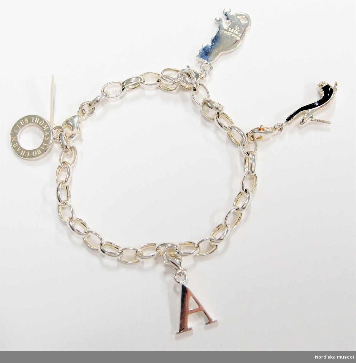 """A)  Armband av silver bestående av länkar med låsanordning i form av liten karbinhake. I ena änden av armbandet en rund platt ring med text """"TEN YEARS CHARM CLUB"""" och på andra sidan """"THOMAS SABO CHARM CLUB"""". Vidhängade  tre löstagbara berlocker med liten karbinhake: Berlock i form av en Damsko i form av sandalett med svarta sidor, hög klack.  Berlock i form av bokstaven A.  Berlock i form av en sittande katt Samtliga berlocker stämplade  """"Ts Ag 925"""" (Thomas Sabo och silverhalt).  B) Förpackning, av kartong överklädd med vaxat papper. Rund med trycklock. Underdel med svart- och vitrandig kant. Undertill vit med inpressad """"Ts"""" inskrivet i en sexkant. Inuti svart med rund del av plast i mitten med text """"THOMAS SABO CHARM CLUB"""" samt """"Thomas Sabo"""" i skrivstil.  C) Vitt lock med svarta text (samma som inuti asken). På insidan svart med vit text """"Thomas Sabo"""" i skrivstil.  D) Påse/förpackning av svart glansigt syntettyg. Rektangulär form. Upptill dragsko av svart tvinnat snöre i sydd kanal. På ena sidan tryckt text i silverfärg """"Thomas Sabo"""" i skrivstil.  E) Broschyr, tryckt på papper. Lång rektangulär remsa vikt i dragspel. Blå yttersidor med text och bild. inuti bilder på armband och berlocker samt text.  På ena yttersidan påklistrad oval etikett i guldfärg med tryck."""