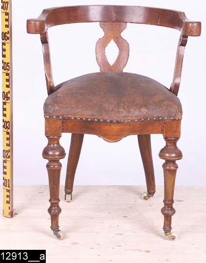 Anmärkningar: Karmstol, omkring 1900.  Rundat, halvåneformat och kontursågat överstycke med voluter på ändarna. Genombruten rygg med S-formiga ryggstolpar (bild 12913__b). Ryggstolparna i mitten är spegelvända, men även dessa är S-formiga. Stoppad sits med läderöverdrag som är fäst i stolen med tännlikor i mässing. Sitsen är fjädrad (bild 12913__c). Kontursågad framsarg. Profilsvarvade framben. Bakbenen är svagt S-formiga (bild 12913__b). Samtliga ben är försedda med hjul på trissor. H:700 Br:650 Dj:485  Hela stolen är av ljust lövträ och är mörkbetsad.  Tillstånd: Del på överstycket saknas, sannolikt skall ryggen vara högre.