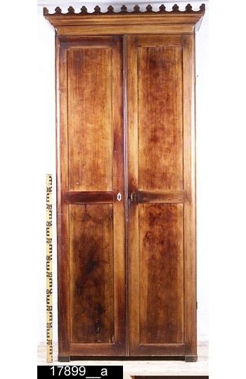Anmärkningar: Klädskåp, mörkbetsad furu, troligen sent 1800-tal.  Gotiskt inspirerat framskjutande krön. Pardörrar med dubbla speglar. Den vänstra dörren har en nyckelskylt i elfenben (bild 17899__d). Invändigt ett hyllplan och två vridbara upphängningsanordningar samt två fasta för kläder (bild 17899__b). På insidan av vänster dörr finns upptill och nedtill dörrsnäppar i mässing. Lås och nyckel i järn. Fyra fötter, de bakre är fyrkantiga och de främre är något rundade. H:2080 Br:930 Dj:360  Tillstånd: Delar av krönet är löst (bild 17899__d). Nyckelskylt saknas på höger dörr. Ett hyllplan saknas. I övrigt har skåpet invändigt en distinkt doft (farmor/farfar), troligen framkallad av doftpåse.  Historik: Inköpt av Fru Gun Skog, Västermalmsgatan 9, Västerås, för 500 kronor.