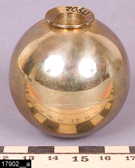 """Anmärkningar: Ljusstake, """"Sfär"""", omkring 1973.  Klotformad ljusstake med en liten ljusmanchett och en omslutande horisontell skåra i mitten. Undertill är ljusstaken märkt SKULTUNA 1607 Sweden P Forssell (Pierre Forssell var formgivare på Skultuna 1955-1986), bild 17902__b. Enligt liggaren upphörde tillverkningen av modellen sfär 1973. Enligt en broschyr, utgiven av museet 2007 och benämnd """"Skultunastämplar 1800-2000"""", började den typ av stämpel som finns på föremålet användas 1922. Den användes fortfarande år 2007.  Tillstånd: Nyskick.  Historik: Inköpt från Holms Glas & Porslinsaffär, Stora Gatan 39, Västerås, för 34,50 kronor 1974."""