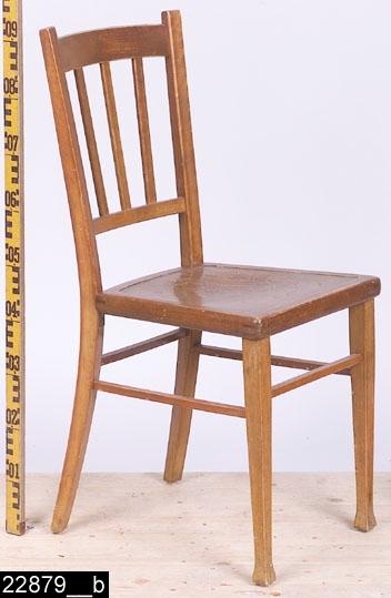 """Anmärkningar: Stol, jugend, omkring 1910.  Svagt konvext överstycke. Svängda bakstolpar (bild 22879__b). Genombruten rygg med tre ryggspjälor som är fästa på en ryggslå. Sits av trä med pressat stilblandat mönster i form av bl.a. slingrande ornament och en fruktskål i mitten och två mytologiska figurer på flankerna (bild 22879__c). Raka framben med fyrkantiga svagt pyramidformade fotavslutningar. Under fotavslutningarna finns runda fotstöd i gummi. Fyra benslåar binder samman benen, dessa sitter i olika höjder. H:930 Br:400 Dj:485  Hela stolen är betsad.  Historik: I kortkatalogen står följande (hämtat från invnr. 22876): """"Inköpta i samband med utställningen """" Bostad """" hösten 1985 från Britta Strandberg, Svartbäcksg. 94a, Uppsala. Ursprungligen inköpta i Lewin Johanssons Möbleringsmagasin i Västerås 1916 av montör Axel Johanzon, Hammarbygatan 2 i Västerås och hans hustru Tekla till deras första hem, som strax därefter flyttades till lantvärnsgatan 14 i Västerås. Köpet omfattade 4 stolar för kronor 24 och var en del av det hela möblemang som inköptes vid samma tillfälle omfattande toalettbyrå, matbord, 4 stolar, soffa, fällbord, soffa, portierer och rullgardiner. Summan kr 315: 30 betalades genom avbetalningar på två år."""""""