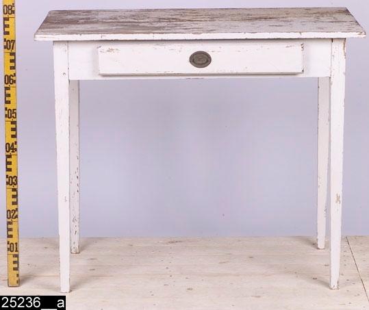 Anmärkningar: Bord, gustaviansk modell, 1800-tal.  Rektangulär bordsskiva. En draglåda med ett mässingsbeslag med motiv av en fruktkorg (bild 25236__b). Fyra nedåt avsmalnande ben. H:770 Br:920 Dj:490  Hela bordet är av ek utom lådan som är av furu. Hela bordet har en sekundär vit målning. Under denna färg finns en vit originalfärg (bild 25236__b).  Tillstånd: Färgen flagnar kraftigt. Mässingsbeslaget saknar handtag.
