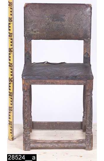 """Anmärkningar: Stol, s.k. åttaslåstol (benämning efter antalet benslåar), senrenässans modell, 1600-tal.  Rektangulär stoppad ryggbricka med läderöverdrag som är fäst i ryggstolparna, överstycket och ryggslån med tännlikor i mässing. Baktill finns, vad som troligen är, ett brännstämplat ägarmonogram """"OAB"""" (bild 28524__c). Sits av trä med läderöverdrag som är fäst i sargarna med tännlikor i mässing. Samtliga sargar är profilerade i nederkanterna. Fyra profilsvarvade ben (bild 28524__b). Fyra kälade fotslåar. H:905 Br:455 Dj:410  Stolen bär spår av olika färger. Dessa är kraftigt slitna, men mörkröd och viss gul färg kan skönjas (bild 28524__c).  Invnr. 701 är enligt liggaren inköpt som en stol. Invnr. 10447 är enligt liggaren inköpt som två stolar. Någon gång har en förväxling uppstått och invnr. 701 har införts i invnr. 10447. Detta är förståeligt då alla tre stolar är identiska med undantaget att invnr. 701 är helt av ek, de andra är av furu. Alla är av senrenässans typ och dekorerna är identiskt utförda. Högst sannolikt är alla tre stolar utförda av samma snickare. I samband med projektet Access genomgång av bl.a. stolar 2006 har invnr. 10447 splittrats, den ena posten har behållit invnr. 10447, den andra fick invnr. 28524.  Tillstånd: Lädret är slitet och skadat.  Historik: Gåva av fru Ida Nygren, Jakobsgatan 2, Västerås."""