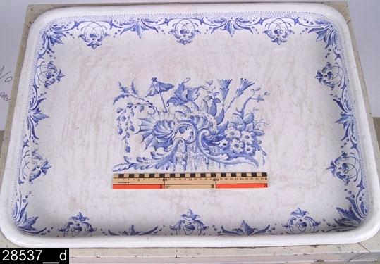 Anmärkningar: Tebord, rokoko/sengustavianskt, målad datering 1762.  Löstagbar bricka av fajans med i mitten ett målat rokokomotiv i form av snäckornamentik, snirkliga blommor och ett paraply (bild 28537__c). Runt brickans innerkant är en blomsterbård målad (bild 28537__d). Under brickan finns en datering (22/4-62, d.v.s. 1762) samt två märken för Rörstrand (bild 28537__b). Före dateringen står bokstäverna St vilket står för Erik Sträng (som levde mellan 1741-1787 och var målare på Rörstrand). Fyra nedåt avsmalnande ben. H:790 Br:740 Dj:565  Brickan är tillverkad enligt datering. Underredet är sengustavianskt och är tillverkat något senare, omkring 1800 . Underredets originalfärg, svart, syns igenom på flera ställen (bild 28537__e). Enligt kortkatalog och liggare har föremålsposten 9936 endast bestått av en bordsskiva i fajans, då det skänktes till museet. Eftersom  9936 är samma föremål som 28537 (samma datering och märkning) måste underredet ha tillkommit senare, möjligen i samband med någon utställning.  Litteratur: Rörstrand under tre århundraden 1726-1943 (Nationalmuseum). Arvid Baeckström, Rörstrand och dess tillverkningar 1726-1926, 1930  Tillstånd: Brickan är sprucken och lagad.