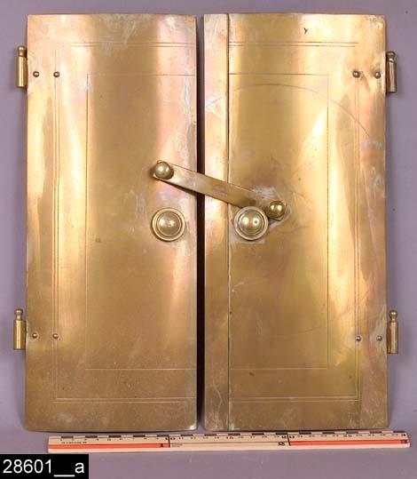 """Anmärkningar: Kakelugnslucka, 1840/1860-tal.  Rektangulär kakelugnslucka i två delar. På sidorna finns vardera två delar som skall fästas i gångjärn. På vardera lucka sitter på mitten en rund knapp. På den högra luckan finns en stängningsanordning som fälls ned över båda luckornas knappar. Anordningen är stämplad med en krona samt texten """"SKULTUNA"""" (bild 28601__b). Liknande kakelugnsluckor finns nämnda och avbildade i priskuranter från Skultuna under 1830-1860-talen. Enligt en broschyr, utgiven av museet 2007 och benämnd """"Skultunastämplar 1800-2000"""", användes den typ av stämpel som finns på föremålet under 1840-1860-talen. H:355 Br:325  Tillstånd: Nyskick.  Historik: Gåva från SAPA AB, Division Service, 2002. Föremålet stod i ett skyddsrum på bruksområdet i Skultuna."""