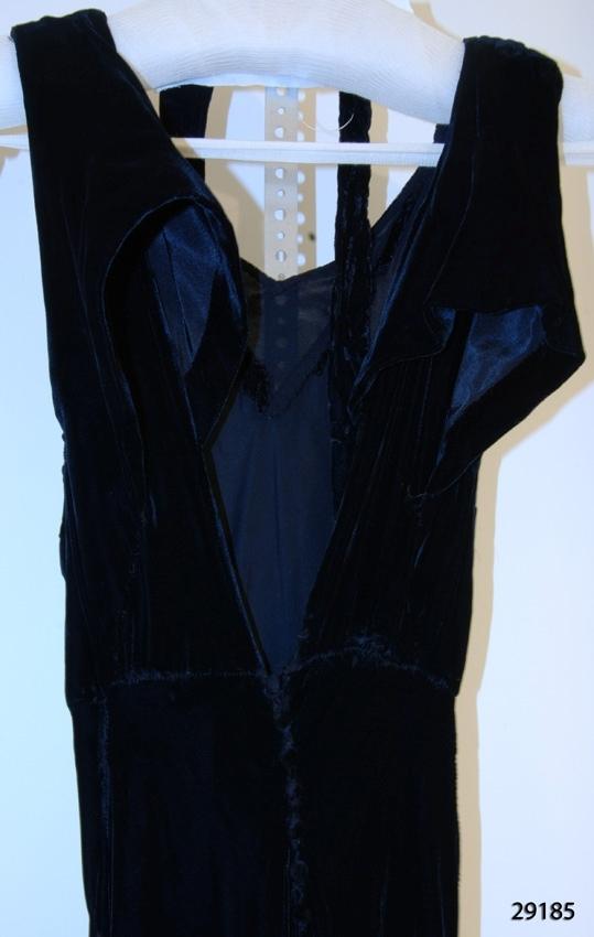 """Anmärkningar: Irsta sn Gäddeholm Använd av Ebba Lewenhaupt gift Linton Geddeholm. Född 1913 död 2007.  Lång svart festklänning av silkessammet. Breda axelband. Rak urringning fram. Djup V-formad urringning bak. Klänningen knäpps med sju sammetsklädda knappar i ryggen mitt bak. Svart knytskärp i samma tyg runt midjan. Klänningen försedd med isytt bomullsband längst ner med texten """"klänningen har legat länge...sammeten kan ångas upp. """" Inga skador."""