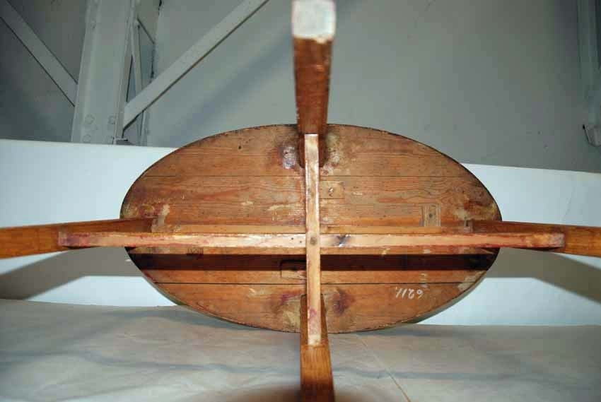 Anmärkningar: Bord, 1800-tal.  Oval bordsskiva. Fyra nedåt avsmalnande ben. Ett ben-kryss förbinder benen. Hela bordet är ådringsmålat, måleriet imiterar ek. Detta måleri är gammalt (sekelskiftet 1800/1900), men ej ursprungligt. Benen har varit rödmålade och bordsskivan svartmålad, dessa färger skymtar fram på flera ställen (bild 6211__b-c). H:730 L:810 Dj:445  Tillstånd: Färgen flagnar kraftigt.  Historik: Gåva från Kungliga Västmanlands Regemente 1928.