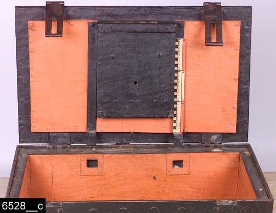 """Anmärkningar: Kassakista av järn, 1700-tal.  Gångjärnsförsett platt lock. Framsidan av locket är försett med dubbla järnhankar där ett hänglås (bild 6528__b) skall fästas. Kortsidorna är försedda med järnhandtag. Invändigt sitter ett stort lås (bild 6528__c). Fyra runda fötter. Hela kistan är indelad i fyrkantiga gröna fält. Två nycklar finns, den ena hör till det stora låset och den andra till hänglåset (bild 6528__b). På en lapp tillhörande nycklarna står det """"Officerskåren I18 / värdekista"""" (bild 6528__b). H:495 L:810 Dj:510  Två kistor har varit försedda med invnr. 6528. Inventarienumret har splittrats av projektet Access under dess genomgång av bl.a. kistor 2007. Den andra kistan har nu invnr. 28544.  Tillstånd: Kistan är ommålad invändigt, troligen även utvändigt. Nyckelhålet på locket går inte att göra synligt p.g.a. att ett beslag har slagit sig och inte går att få upp (bild 6528__d), därmed kan man inte heller föra in nyckeln och låsa kistan.  Historik: Har tillhört Folkare kompani. Gåva från Kungliga Västmanlands Regemente 1928."""