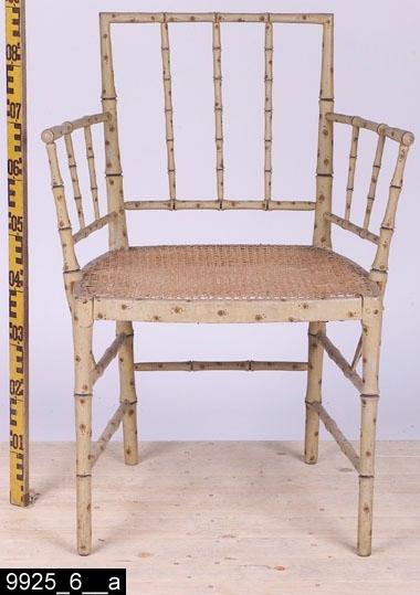 """Anmärkningar: Karmstol, av Ephraim Ståhl, omkring 1800.  Rakt överstycke. Svängda bakstolpar. Genombruten rygg med tre ryggspjälor och en ryggslå som ryggspjälorna är fästa i. På vardera sida finns ett armstöd som är fästa i bakstolparna. Armstöden är genombrutna och består av två vågräta spjälor och två lodräta spjälor samt en lodrät spjäla som sträcker sig ned till den översta benslån. Flätad rottingsits. I båda hörnen av baksargen finns Ephraim Ståhls signatur stämplad """"ES"""" (bild 9925_6__c, visar signaturen på den högra delen, signaturen är stämplad uppochned). På insidan av baksargen finns Stockholm stolmakarämbetes etikettsigill (bild 9925_6__d). Utåtsvängda bakben (bild 9925_6__b). Raka framben. En benslå mellan bakbenen. Mellan frambenen och bakbenen finns på vardera sida två benslåar. H:865 Br:630 Dj:500  Hela stolen är svarvad (utom sargarna) och målad för att imitera bambu. Möblerna i serien 9925:1-12 söker imitera bambu. Sådana möbler har i omgångar varit populära i Sverige alltsedan kinasvärmeriet från mitten av 1700-talet till sekelskiftet 1800/1900. Enligt litteraturen på området tillverkades möblerna ofta för lusthus, en uppgift som också stöds av proveniensen från museets möbler - de har enligt liggaren stått i ett lusthus på herrgården Gideonsberg (riven på 1950-talet)! Invnr. 9925:1-6 är tillverkade av Ephraim Ståhl (1767-1820), mästare i Stockholms stolmakarämbete 1794-1820. Ståhl var den sengustavianska tidens kanske mest anlitade stolmakare, bl.a. hade han under några år inte mindre än åtta gesäller och tre lärlingar anställda. En omfattande produktion spreds till bl.a. departement, herrgårdar och slott.  Litteratur: Om Ephraim Ståhl se Eva Nordenfelt, Ephraim Ståhl : en kunglig stolmakare, 2007, s166-171. Några av museets möbler finns avbildade på s.168-169. Se även Torsten Sylvén, Stolens guldålder; stolar och stolmakare i Sverige 1650-1850, 2003, s203. Om bambumöbler se nämnda bok av Nordenfelt. Se även Britt Thunander, Illustrerat antiklexik"""