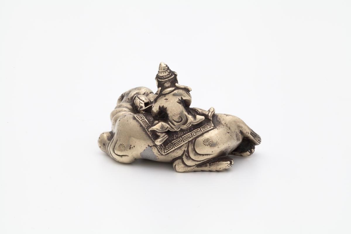 Skulpturen forestiller en mannsfigur som sitters skrevs over ryggen på en liggende elefant. Han er ikledd romslige gevanter og en hatt. Han sitter på et klede med meanderbord og holder i en lotus med begge hendene. Elefanten er dekorert med 6 stjerner.