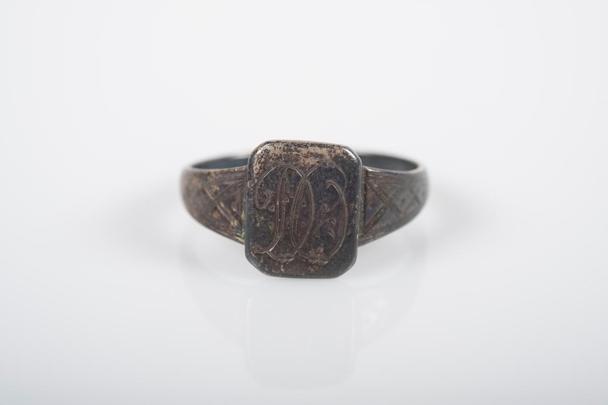 Rund ring i med et firkantet monogram hvor initialene D.O er inngravert. På innsiden står det Grini 1943.