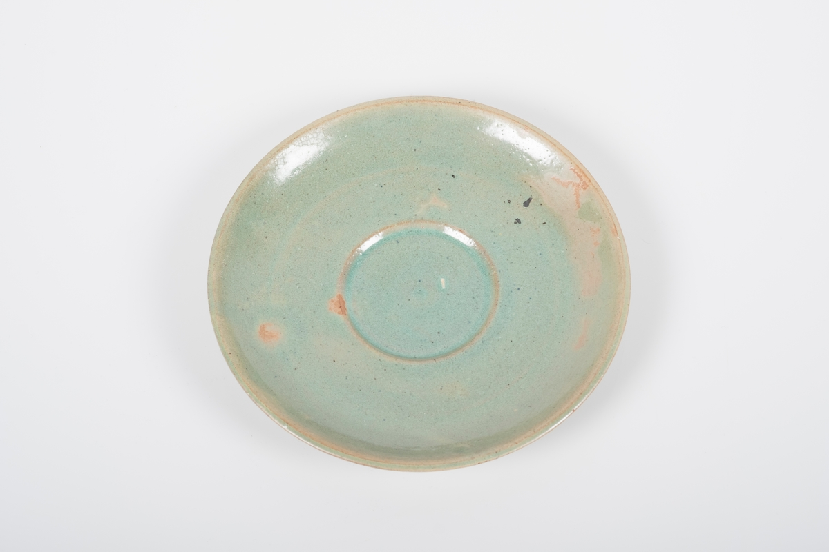 Skål i keramikk med grønn lasur. Spor etter tre knotter på bunnen, usikker funksjon. Bunnen har matt overflate.