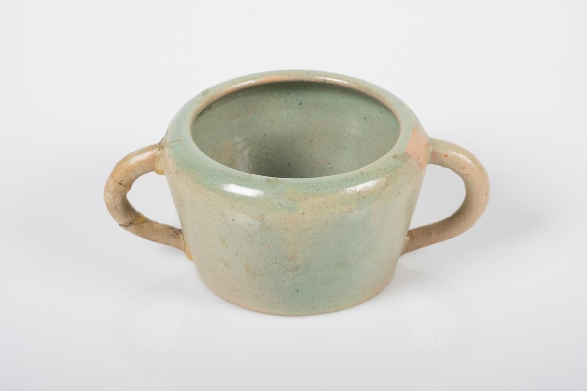 Sukkerkopp i keramikk med grønn lasur. Blanke overflate på innsiden, matt overflate på utsiden. 2 buede hanker. Spor etter 2 små knotter på bunnen, usikker funksjon.