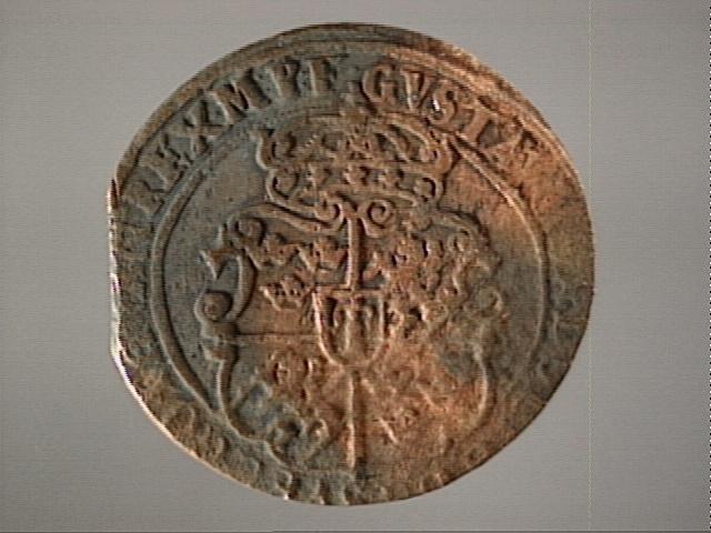 1 öre Runt mynt Åtsidan: mitt på myntet det svenska riksvapnet, svagt synligt. Omskriften med Gustav Adolfs regent titlar delvis synlig. Ocentrerad prägling. Frånsidan: en grip i vänsterprofil, svagt synlig. Till vänster om gripen siffran 1, till höger versalerna ÖR, svagt synliga. Omskriften på latin med bland annat präglingsåret i romerska siffror, 1627, är delvis läslig. Ocentrerad prägling. Nuvarande skick: bägge sidor slitna. Vikt: 23,1 gram.  Text in English: Round coin. Denomination: 1 öre. The obverse side has the Swedish coat-of-arms in the centre, faintly legible. The legend has the regent titles of Gustav Adolf of which the latter is partly visible. The coin stamp is off-centre. The reverse shows a griffin in left profile, faintly visible. On the left-hand side is the numeral 1 and to the right the initials ÖR. which appear in capital letters, faintly legible. The legend has a Latin inscription and the year of coinage, 1627, in Roman numerals. The Latin inscription on the legend is faintly visible. The coin stamp is off-centre. Present condition: both sides are worn. Weight: 23,1 gram.