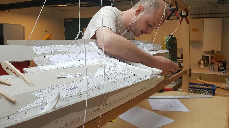 Arkeolog bøyer seg over og arbeider på innsiden av en uferdig båtmodell i plast og papp. Modellen er støttet opp i en treramme ved hjelp av klemmer og klyper i tre og plast, samt snører på flere steder.