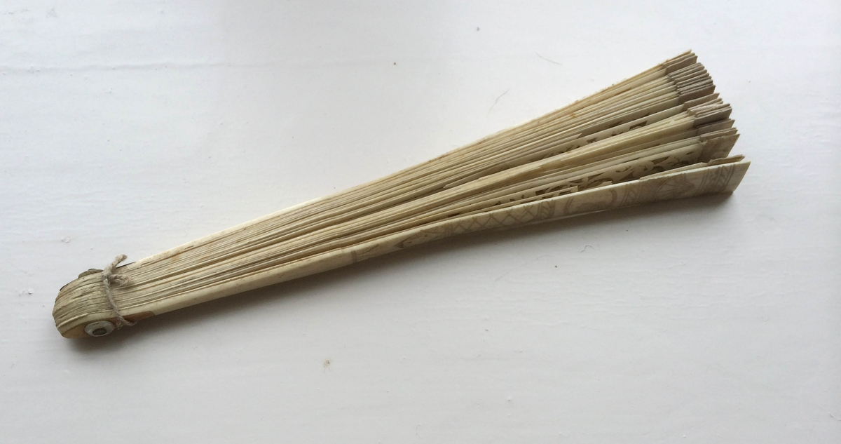 Vifte av ben, spiler og plate i ett, kantet med hvitt silkebånd øverst. Den del som danner platen er rikt utskåret, gjennombrutt i et rankemønster. Endespilene har et innrisset rute-, strek- og skjellmønster.