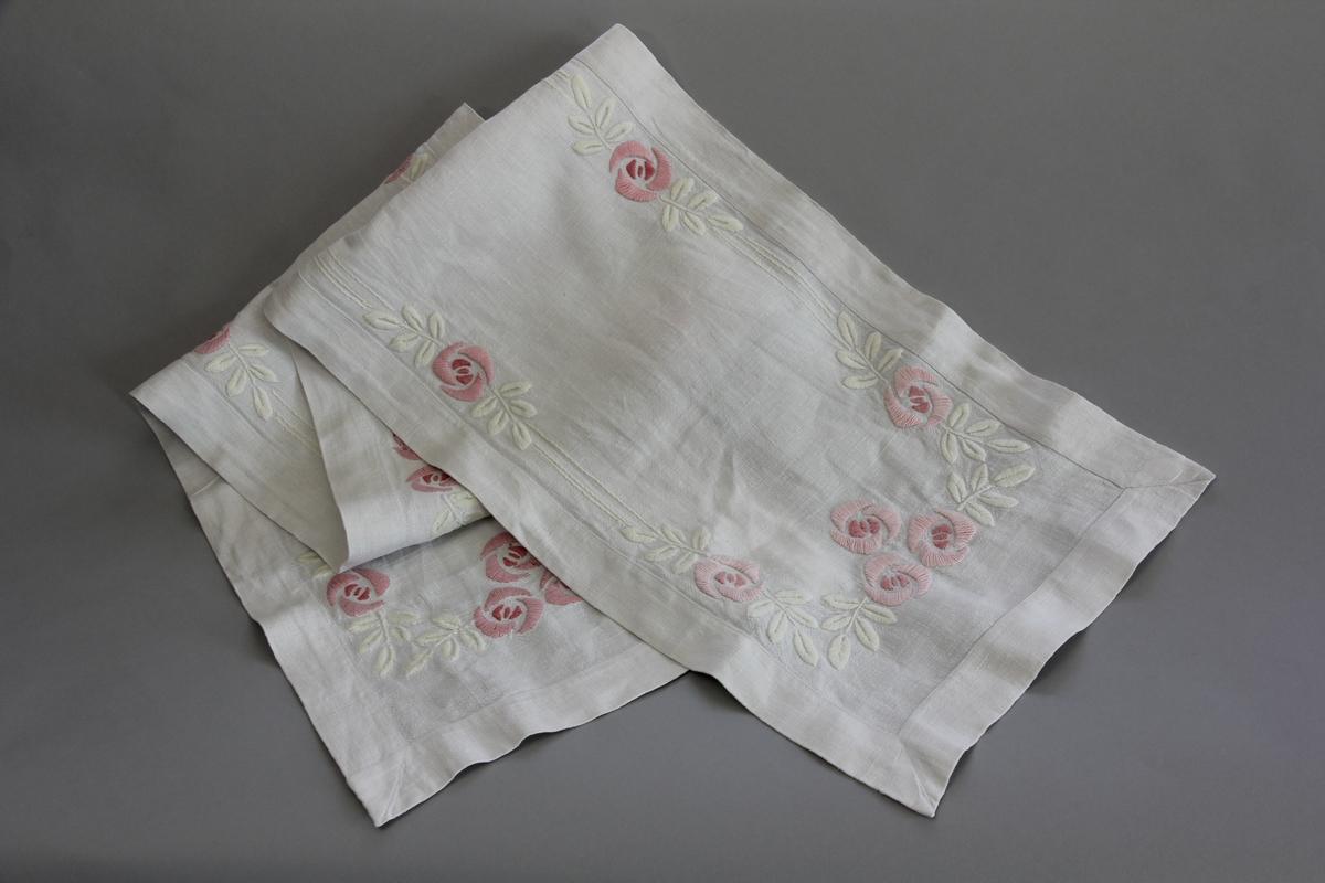 Duk, avlång, av vitt halvlinne. Broderade vita blad i plattsöm och broderade blommor i två nyanser rosa i plattsöm.