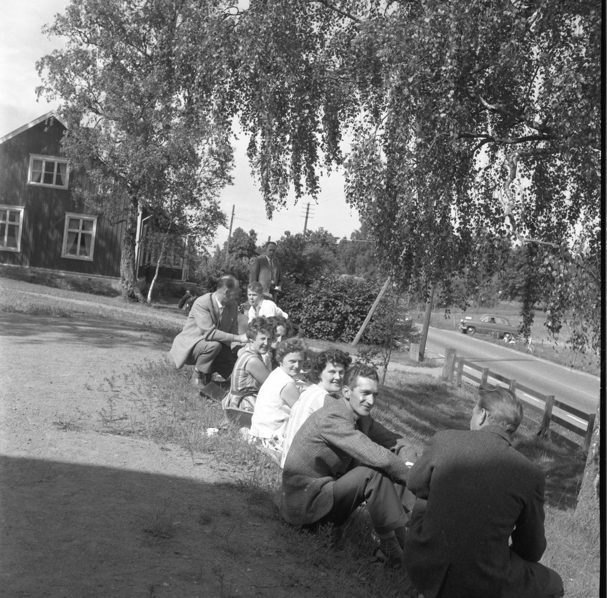 Skolträff i Reaby 1962. Kvinnor och män sitter på en slänt söder om skolbyggnaden utmed riksettan. Två fr höger sitter Karl-Gustav Johansson och intill honom Märta Nilsson, därnäst Ingegerd Gustavsson från Askarp.