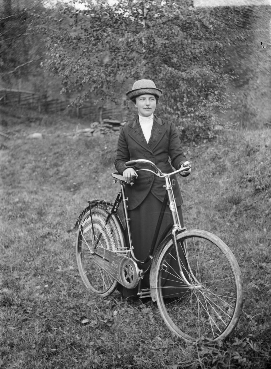 """Kvinne med sykkel, merk """"Tryg"""""""