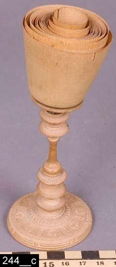 Anmärkningar: Ask, 1800-talets senare hälft.  Svarvad rund ask med lock. Hela asken är försedd med skurna detaljer (bild 244__a-b). I asken ligger en svarvad miniatyrpiedestal med skurna dekorer (bild 244__c). Till piedestalen hör ett femtiotal synnerligen tunt svarvade bägare (bild 244__c-d). H:175 D:90  Kan möjligen ha varit ett mästarprov.  Tillstånd: Miniatyrpiedestalen är trasig.