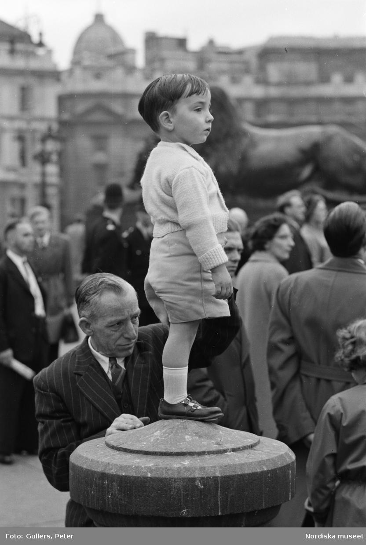 London. En pojke i ljusa kläder står på en plint.