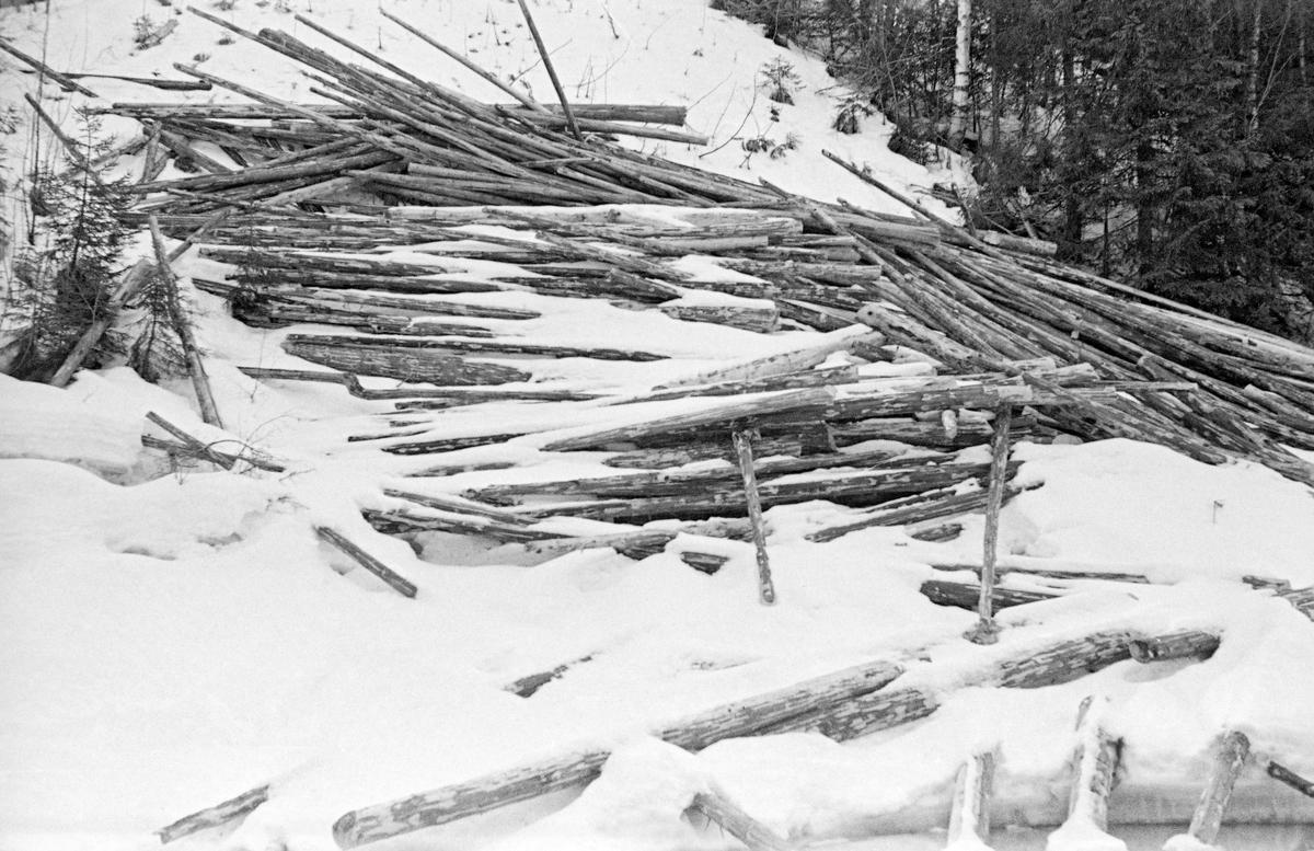 Vinteropptak av tømmervelte i Hovda-vassdraget i Åmot i Østerdalen.  Fotografiet er tatt på tvers av et is- og snødekt elveleie mot en forholdsvis bratt elveskråning, der barket tømmer øyensynlig er rullet ned mot elveleiet i løpet av vinteren.  Stokkene ligger noe hulter til bulter, men i hovedsak parallelt med vassdragets strømretning.  Bakenfor velta, øverst til høyre i bildeflata skimtes forholdsvis tett granskog.  Bildet ble tatt i april 1952.  Dette var en måte å levere tømmer på som Glomma fellesfløtingsforening ønsket å komme bort fra på dette tidspunktet, jfr. SJF. 1990-00300. Hovda og dens sideløp har et samlet nedslagsfelt på drøyt 190 kvadratkilometer.  Elva er fløtbar fra innsjøen Storhovden og nedover, men tømmer som ble levert på den øvre delen av denne strekningen nådde ikke alltid fram til Glomma i løpet av en sesong.  Først fra sammenløpet med sideelva Hemla og østover ble fløtinga i Hovda ansett for å være «årssikker».