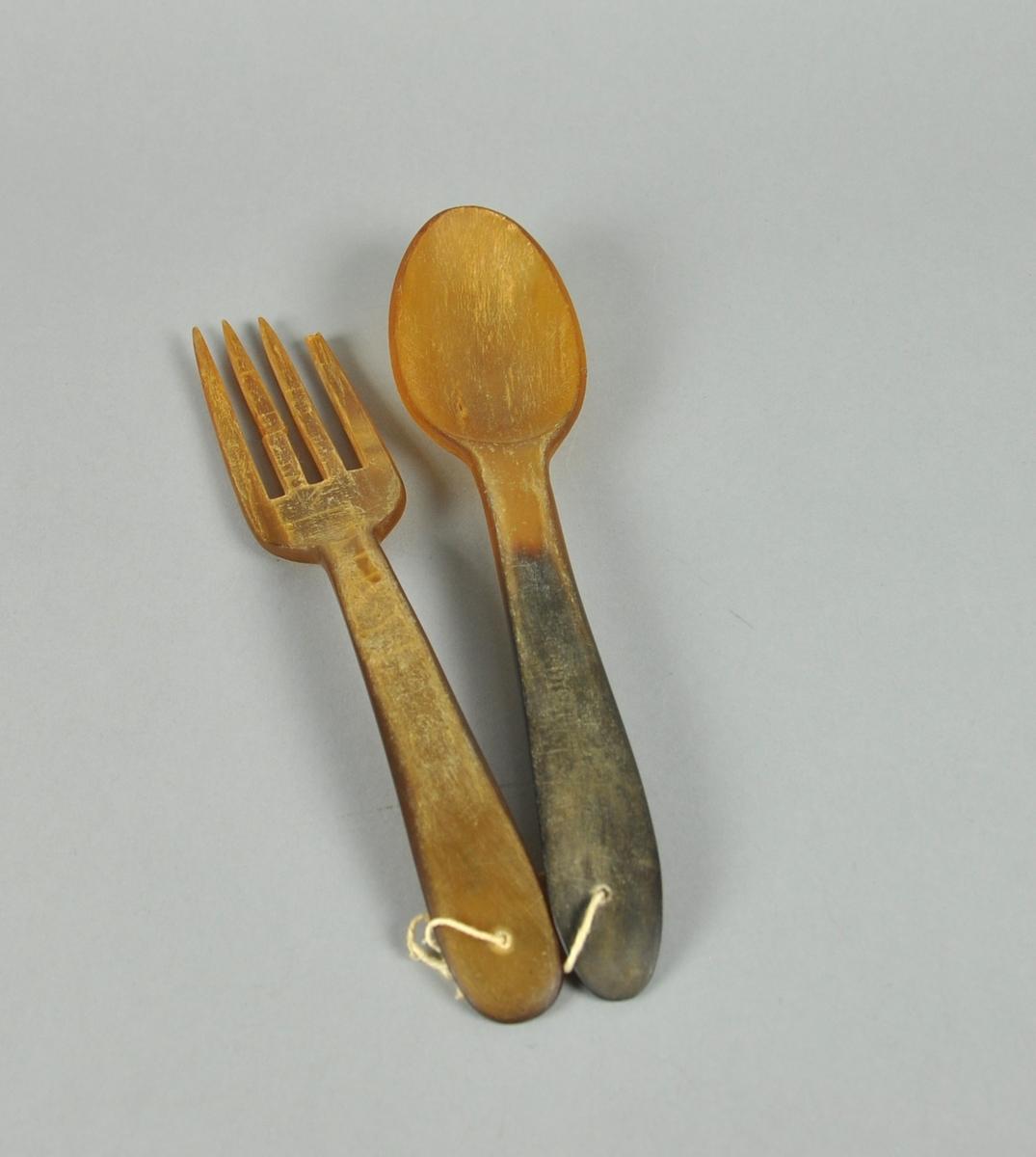 Salatbestikk av horn eller bein, bestående av en gaffel og en skje.