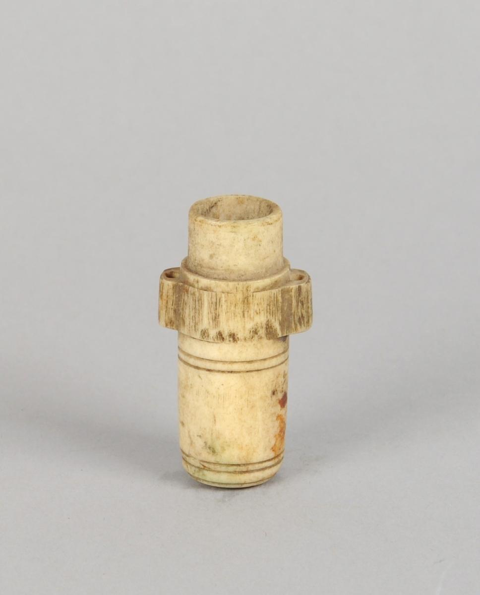 """Uthulet og sylinderformet gjenstand av bein, med """"hank"""" på hver side. Gjenstanden er tett i den ene enden."""