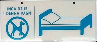 """Dubbelsidig rektangulär skylt av inplastat papper med blått tryck på vit botten. Text på skylten: """"INGA DJUR I DENNA VAGN"""". Överstruken stiliserad hund i cirkel. Stiliserad bäddad säng. Två hål i överkanten för upphängning. Avsedd för sovvagn."""