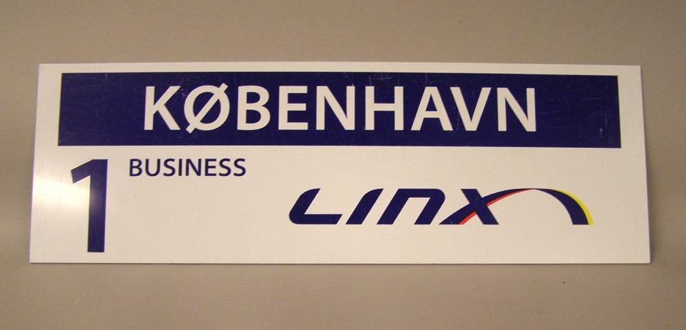 """Rektangulär liggande plastskylt med blått tryck på vit botten. Destinationsskylt från bolaget Linx. Vit botten med texten """"Linx"""" med blå bokstäver. Över detta ett blått fält med texten """"Köbenhavn1 business"""". Skyltens andra sida har blå botten och text 1 Linx och en vit bård.  Historik: Tågbolaget Linx bildades 2000 och påbörjade sin trafik 2001. Linx körde den gränsöverskridande tågtrafiken i den skandinaviska huvudstadstriangeln med undantag av Stockholm-Köpenhamn. Huvudkontoret låg i Göteborg. Linxnätet omfattade sträckorna Stockholm-Karlstad-Oslo och Oslo-Göteborg-Malmö-Köpenhamn. Under de första åren körde Linx en brokig samling av tåg med lokdrivna InterCity-tåg, vanliga X2000 samt även nattåget mellan Malmö och Oslo. Efter hand lades nattåget ner, och så småningom körde man en enhetlig flotta bestående enbart av helrenoverade X2-tåg under det egna varumärket Linx. Linxtåg användes även i trafiken Oslo-Trollhättan-Göteborg under 2004, med en restid på 3.35. På grund av dålig lönsamhet lades Linx ned vid årsskiftet 2004-2005."""